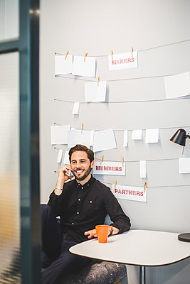 Creative businessman smiling while talking on mobile phone at desk in office - p426m2033464 by Maskot
