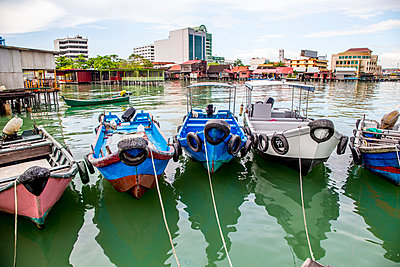 Fishing boats docked in urban harbor - p555m1419521 by Inti St Clair
