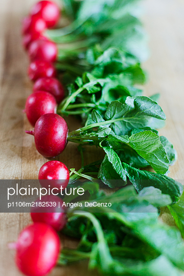 A row of radishes placed on wooden cutting board - p1106m2182539 by Angela DeCenzo