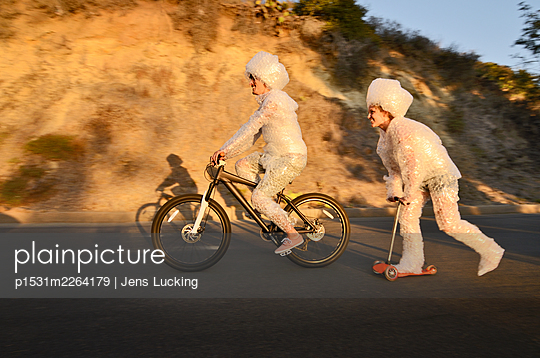 Couple Wrapped In Bubble Wrap Riding On Road - p1531m2264179 by Jens Lucking