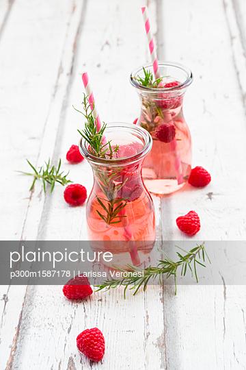 Two glass bottles of homemade raspberry lemonade flavoured with rosemary - p300m1587178 von Larissa Veronesi
