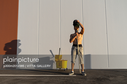 Acrobat playing with cleaning bucket and mop - p300m2012385 von VITTA GALLERY