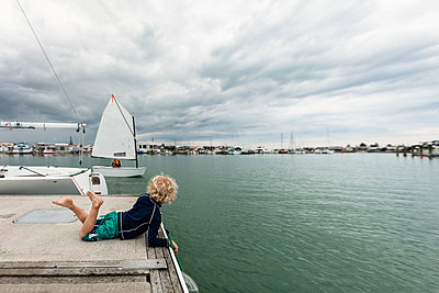 Young child watching a sailboat in Napier New Zealand - p1166m2124103 by Cavan Images