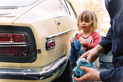 A father and his toddler daughter washing a classic car together. - p1166m2190682 by Cavan Images