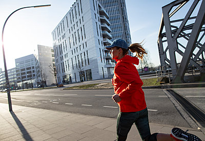 Woman jogging in Hamburg - p1678m2262239 by vey Fotoproduction