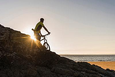 France, Crozon peninsula, mountainbiker looking at sunset - p300m1175972 by Uwe Umstätter