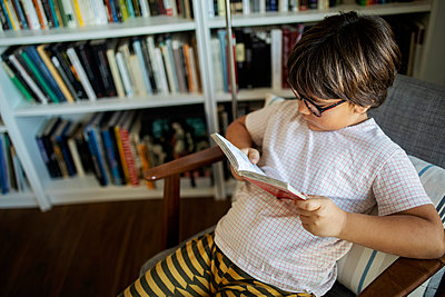 Boy with glasses sitting on armchair reading book - p300m2167081 by Valentina Barreto