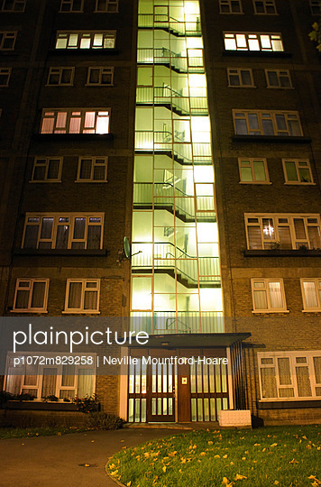 View looking up towards a block of flats at night - p1072m829258 by Neville Mountford-Hoare