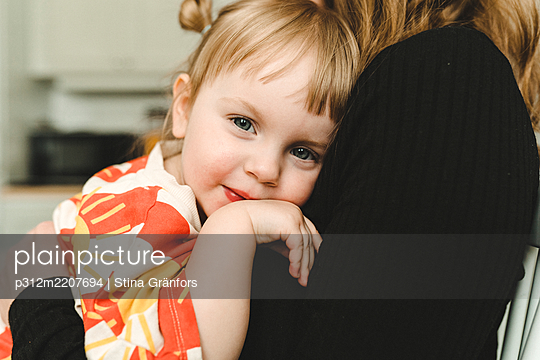 Girl in mothers arms looking at camera - p312m2207694 by Stina Gränfors