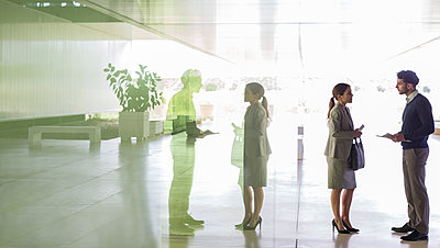 Business people talking in office lobby - p1023m1519830 by Martin Barraud