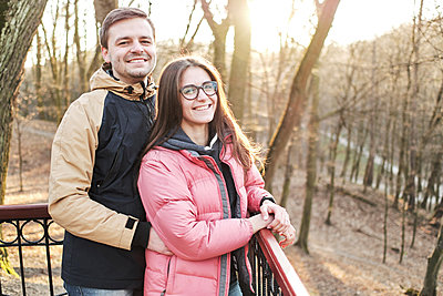 Young loving couple enjoy the sun and warm stroll in the spring park - p1166m2177284 by Cavan Images