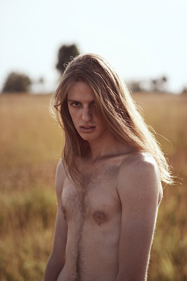 Sensual portraits of man with long hair on field - p1561m2132721 by Andrey Cherlat