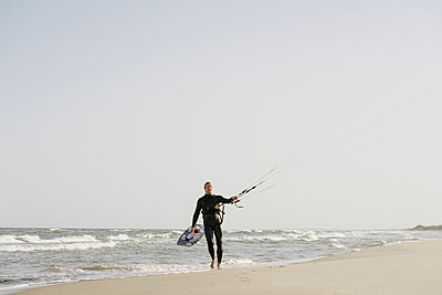 Kiteboarder walking with his kite at the beach - p300m2118710 by Hernandez and Sorokina