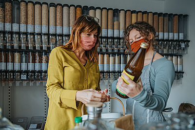 Store clerk and woman shopping in zero waste shop, Cologne, NRW, Germany - p300m2256373 von Mareen Fischinger