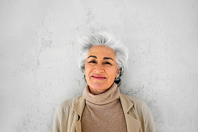 Woman with gray hair smiling in front of wall - p300m2281493 by PICUA ESTUDIO