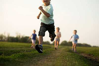 Low view of a boy running in a field with other children behind - p301m714443f by Vladimir Godnik