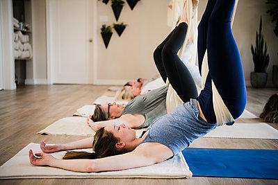 Women doing aerial yoga at retreat - p429m2019509 by Hugh Whitaker