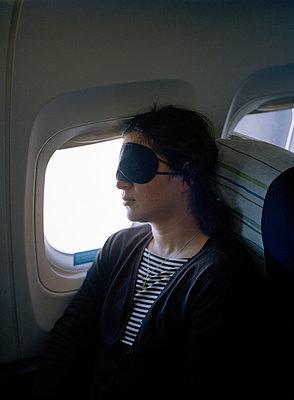 A Scandinavian woman sleeping in an airplane - p5280114f by Elliot Elliot