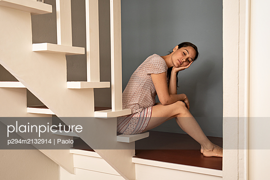 Tired woman with brown hair sits on stairs - p294m2132914 by Paolo