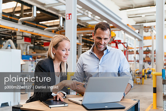 Smiling businessman and female entrepreneur using laptop at factory - p300m2240127 von Daniel Ingold