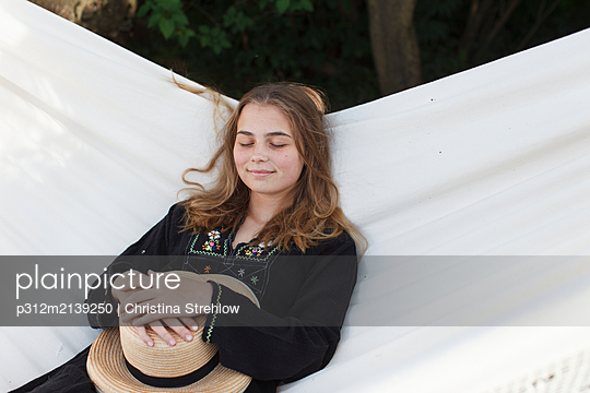 Teenage girl relaxing on hammock - p312m2139250 by Christina Strehlow