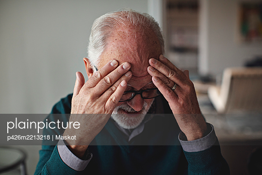 Worried senior man with head in hands at home - p426m2213218 by Maskot
