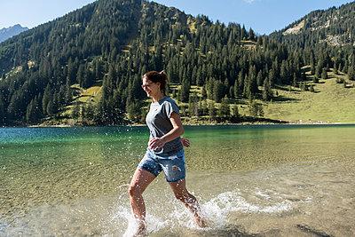 Junge Frau hat Spaß im Wasser an Bergsee - p1142m2053792 von Runar Lind