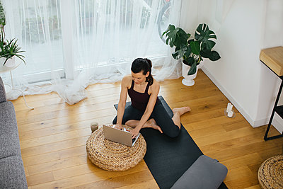 Woman sitting on gym mat at home using laptop - p300m2121820 by Sofie Delauw