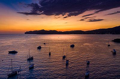 Spain, Mallorca, Santa Ponsa, Aerial view of boats floating in coastal water at dusk - p300m2160181 by Martin Moxter