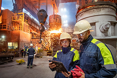 Male and female steelworkers using digital tablet during steel pour in steelworks - p429m2135023 by Monty Rakusen