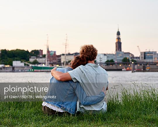 Paar sitzt am Elbufer mit Blick auf den Michel - p1124m1150178 von Willing-Holtz