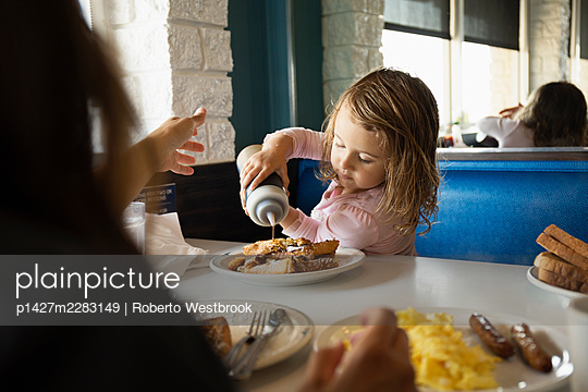 Mother with toddler daughter pouring ketchup in diner - p1427m2283149 by Roberto Westbrook
