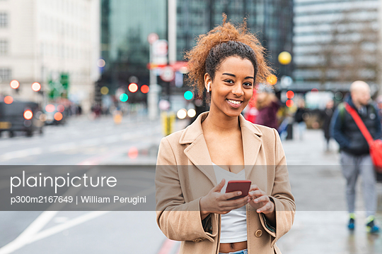 Smiling young woman with cell phone and earbuds in the city, London, UK - p300m2167649 by William Perugini