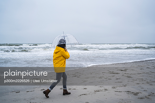 Woman in yellow raincoat walking with umbrella at sea shore against sky - p300m2226526 by Uwe Umstätter