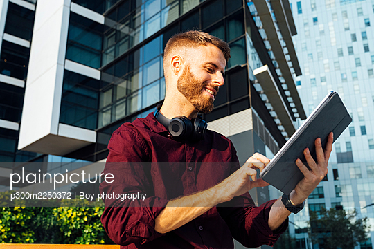 Businessman smiling while using digital tablet standing in city - p300m2250372 by Boy photography