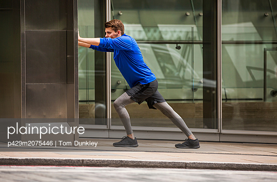 Young runner stretching on pavement, London, UK - p429m2075446 by Tom Dunkley