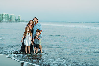 Portrait of family of four in ocean at dusk smiling at the camera - p1166m2136556 by Cavan Images