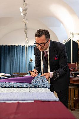 Senior male tailor comparing fabrics - p1166m2261414 by Cavan Images
