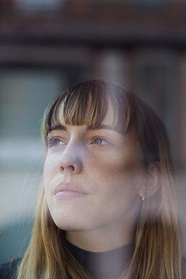 Attraktive, junge Frau mit Pony sieht durch ein Fenster, indem sich eine Häuserwand spiegelt   - p1301m2021007 von Delia Baum