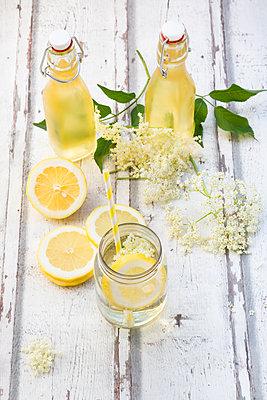 Homemade elderflower sirup, lemon slices, leaves and elderflower - p300m2005520 by Larissa Veronesi