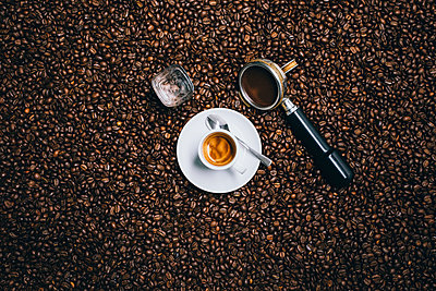 Directly above shot of espresso cup with filter on roasted coffee beans - p301m1498796 by Norman Posselt
