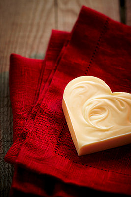 Heart shaped white chocolate on a red napkin - p968m658840 by Roberto Pastrovicchio