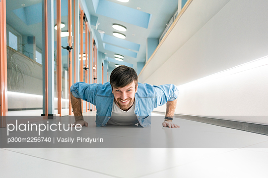 Smiling businessman doing push ups in office corridor - p300m2256740 by Vasily Pindyurin