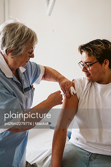 Senior female doctor injecting male patient at medical clinic - p426m2279774 by Maskot