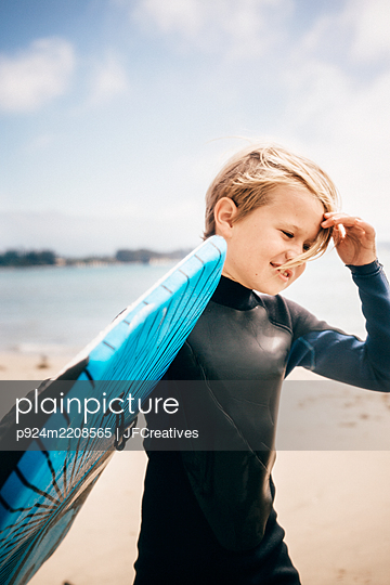 Portrait of young boy wearing wet suit, carrying surfboard into ocean, Santa Barbara, California, USA. - p924m2208565 by JFCreatives