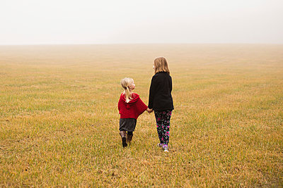 Rear view of siblings walking on field during foggy weather - p1166m1524982 by Cavan Images