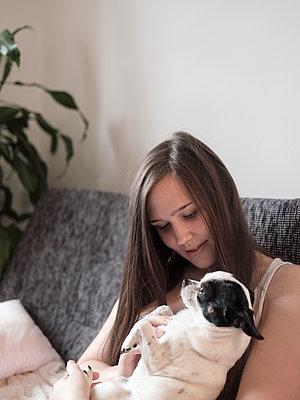 Junge Frau mit Hund am Sofa - p1383m2045122 von Wolfgang Steiner