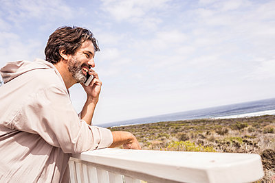 Man wearing bathrobe and phoning with smartphone on a terrace - p300m2167493 by Floco Images