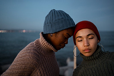 Woman leaning on friend head while standing against sea - p300m2243468 by Rafa Cortés