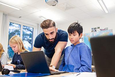 Teacher helping schoolboy in classroom - p312m2191314 by Scandinav